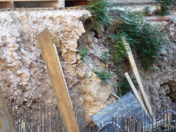 شبه قناطر حجرية وعمود آخر لا تزال مدفونة داخل التراب تظهر في الجوانب المحيطة بالموقع